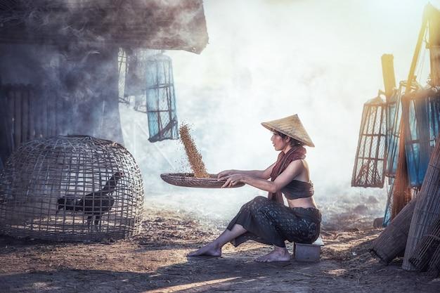 女性は米と籾殻の間に別の米を磨く
