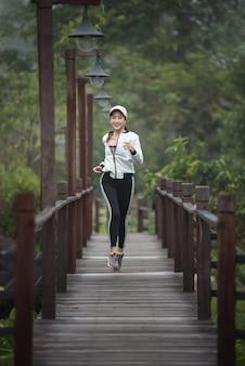 木製の橋で走っている若い女性