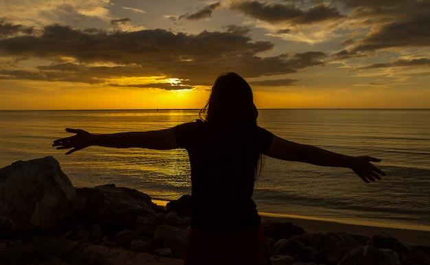 Силуэт женщины молятся за красивый закат фоне