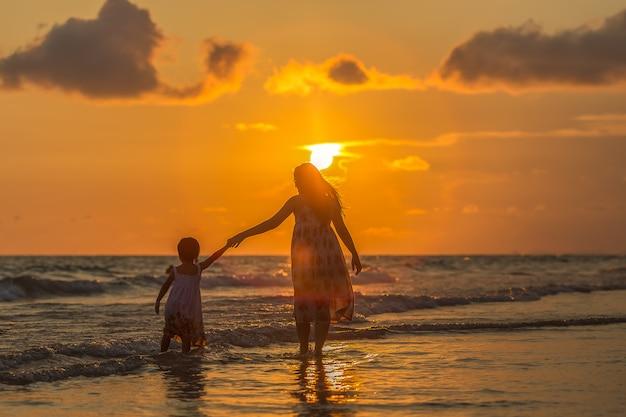 ビーチで彼女の娘を持つ母