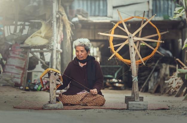老婦人たちがタイシルク織りの手順を実演