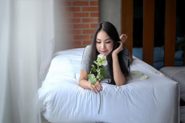Женщина улыбается мечтать и отдохнуть в постели с розой