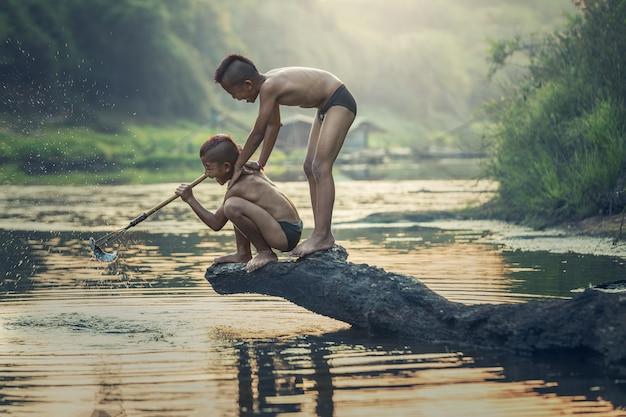 アジアの少年が川で釣り