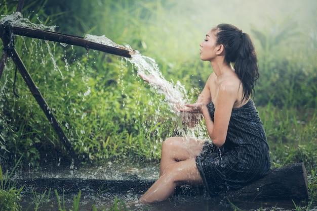 Красивая молодая женщина принимает ванну, естественно течет из бамбукового желоба