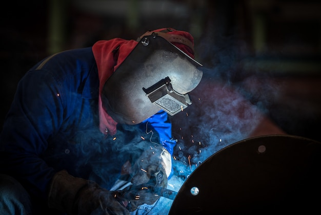 工場での産業用溶接作業員、安全防護マスク付き鋼鉄ジョイントの溶接