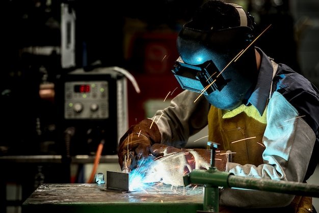 工場での産業用溶接作業員、安全防護マスク付き鋼の溶接