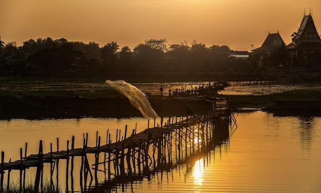アジアの漁師が湖で橋釣り