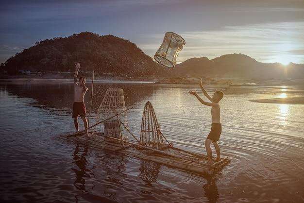 子供漁師の男の子は湖の川タイで魚を捕まえて