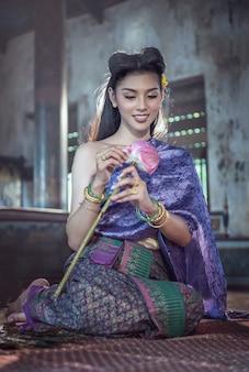 タイの伝統的なドレスを着てアジアの女性は、蓮の花を保持する手