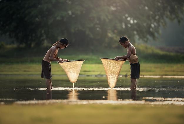 アジアは湖で釣りをする少年たち