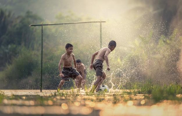 Мальчик пинает футбольный мяч