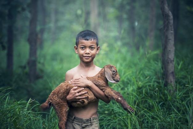アジアの少年が牧草地でヤギの赤ちゃんと一緒に保持しています。