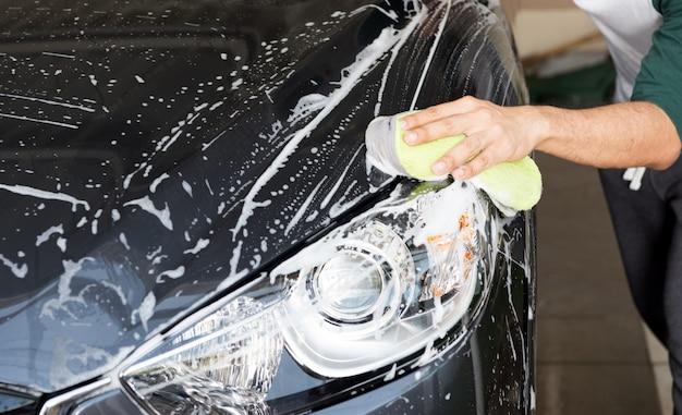 手を洗うために車の上にスポンジを握る