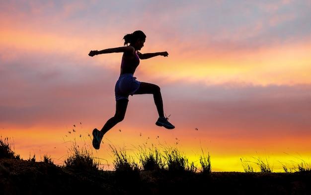 歩道を走っている女性ランナーの運動選手。女性フィットネスジョギングトレーニングウェルネスコンセプト