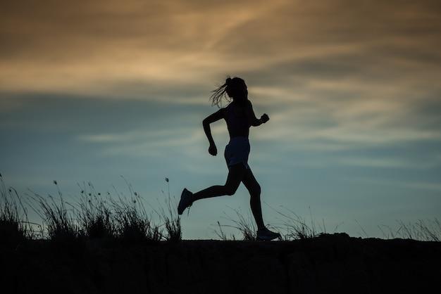 トレイルで実行されているランナーの運動選手。女性フィットネスジョギングワークアウトウェルネスコンセプト。