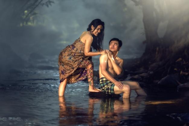 アジアのカップルがタイの田舎でカスケードで入浴