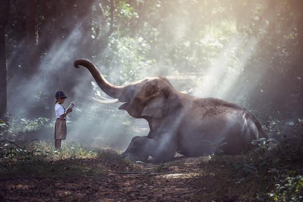 タイの農村の学生象、スリン、タイで書籍を読む。