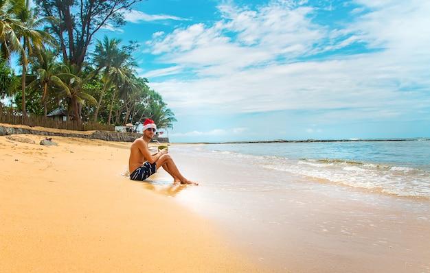 Человек в новогодней шапке на пляже