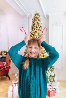 クリスマスキャンデー杖を持つ子ども。セレクティブフォーカス。