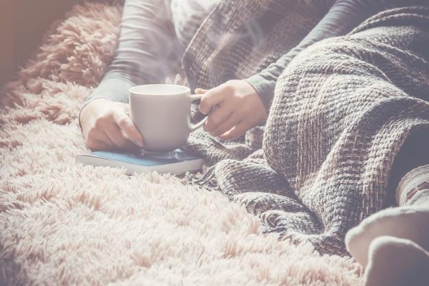 ナヤのカップを持つ少女は毛布の下にあります。セレクティブフォーカス