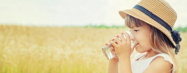 子供が畑の背景で水を飲む。