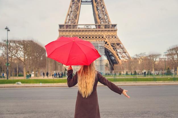 Девушка с красным зонтиком возле эйфелевой башни в париже. выборочный фокус.