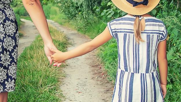 Ребенок идет рука об руку со своей матерью. выборочный фокус.