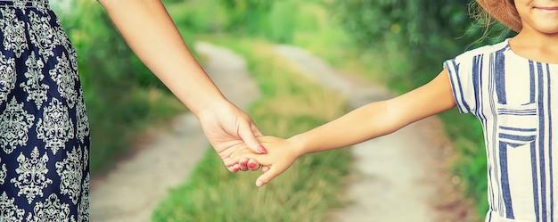子供は母親と手をつないで行きます。セレクティブフォーカス。