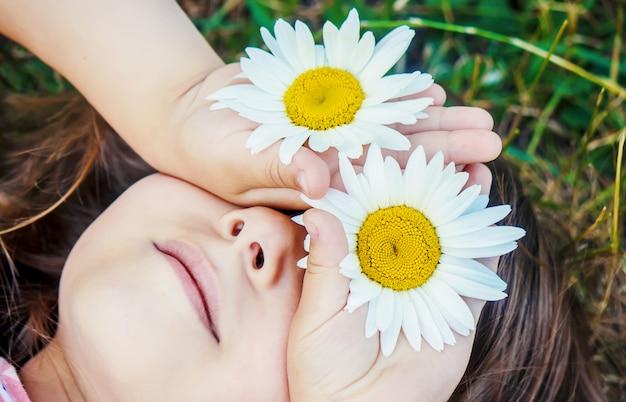 カモミールを持つ少女。セレクティブフォーカス自然の花。