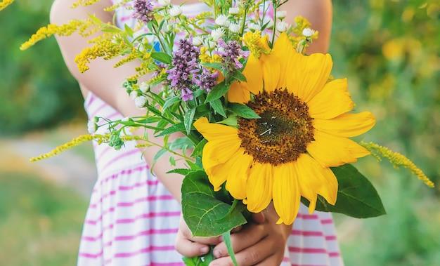 子供は彼の手で野生の花の花束を保持しています。セレクティブフォーカス。