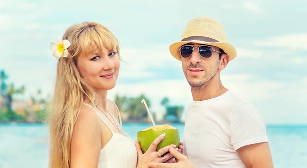 Мужчина и девушка на пляже пьют кокос