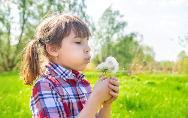 Ребенка девушка с одуванчиками в парке. выборочный фокус.