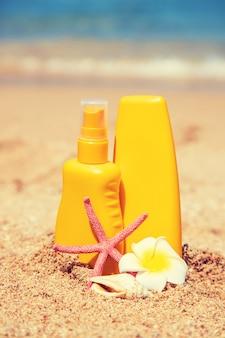 Бутылки солнцезащитного крема и морская звезда на пляже