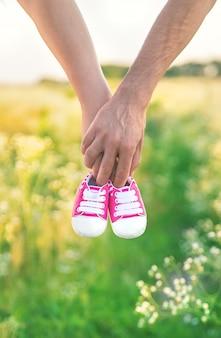 Беременная женщина и мужчина провести детскую обувь природы.
