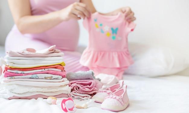 Беременная женщина складывает детские вещи
