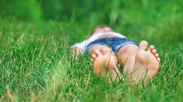 公園の緑の芝生に子供の足。