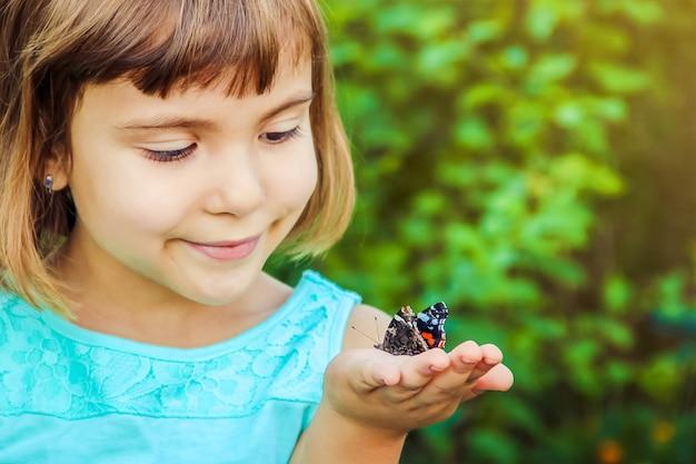 蝶を持つ子供。セレクティブフォーカス自然。