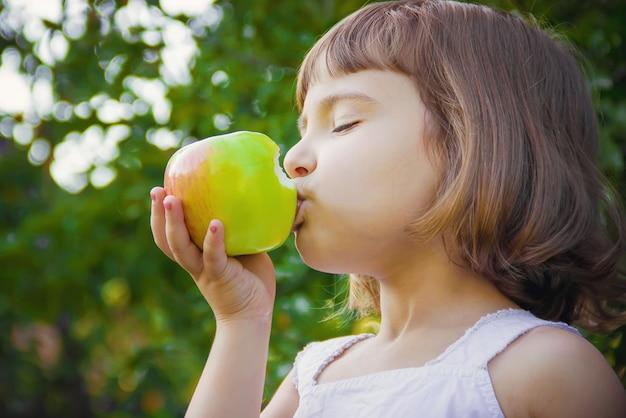 りんごを持つ子供。セレクティブフォーカス自然