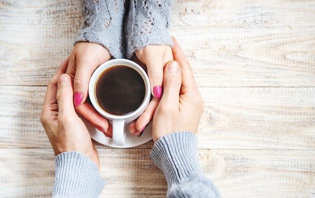 恋人の手に朝食のためのカップドリンク。選択フォーカス。