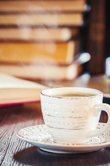 職場でのコーヒーの朝。本やノートパソコンで。セレクティブフォーカス