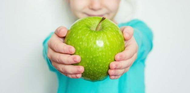 Ребенок с яблоком. выборочный фокус. природа
