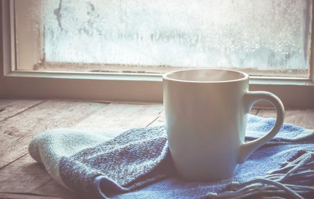 窓の近くの鍋に熱いお茶。セレクティブフォーカス