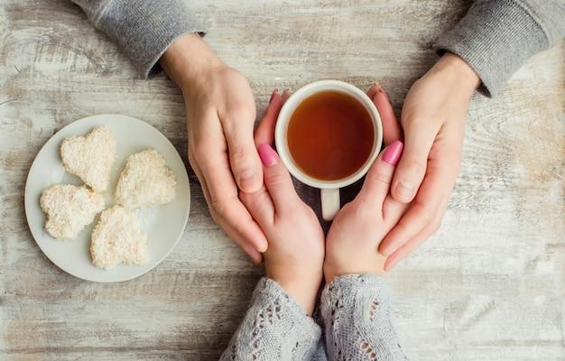 一杯のお茶を一緒に持っている恋人たち。セレクティブフォーカス