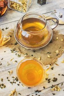 ジャスミンの緑茶と明るい背景に小さなカップの透明なレモンと黒。ティーメーカーセレクティブフォーカス