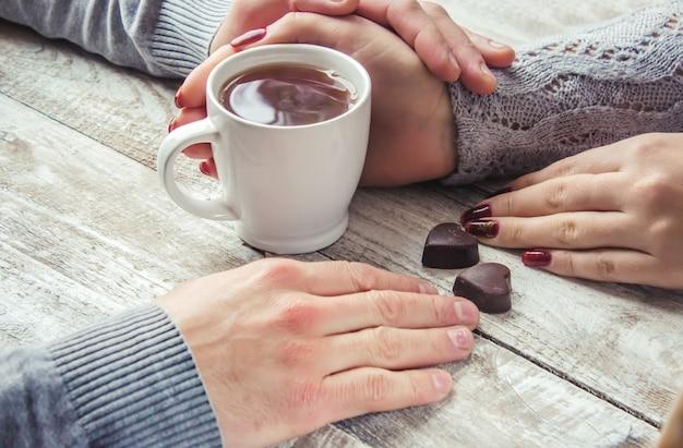 Влюбленные держат вместе чашку чая. выборочный фокус.