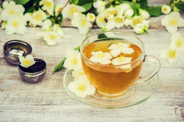 Чашка травяного чая с цветами жасмина. выборочный фокус.