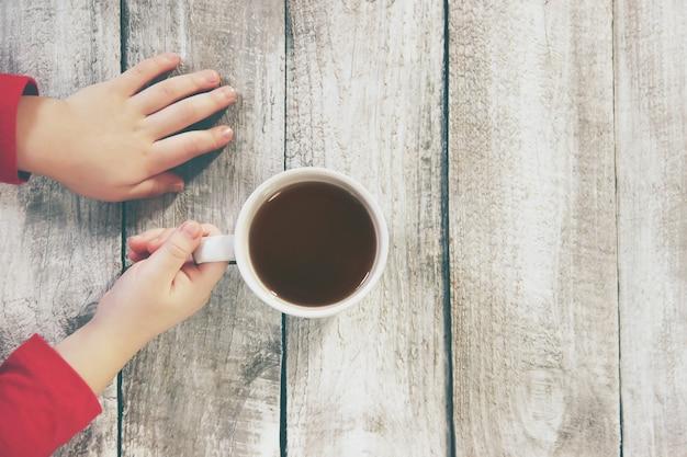 子供の手の中にお茶を一杯。快適さ