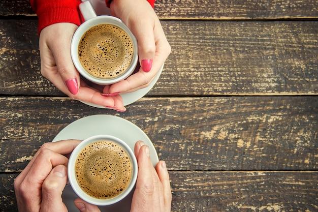 Чашка напитка на завтрак в руках влюбленных. выборочный фокус.