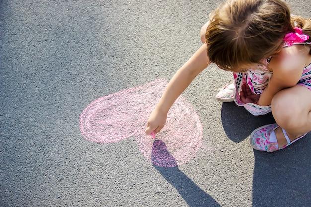 子供はアスファルトの心にチョークを塗ります。セレクティブフォーカス