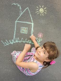 子供はアスファルトの上にチョークで家を描きます。セレクティブフォーカス